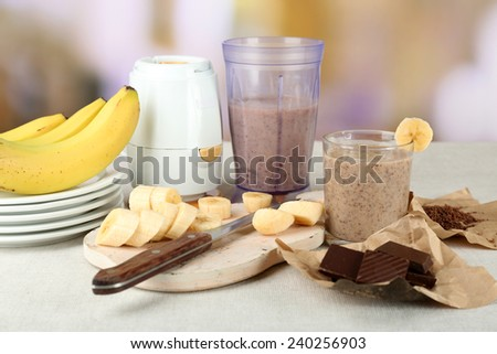 Sliced banana on cutting board and chopped chocolate, on wooden table, on bright background - stock photo