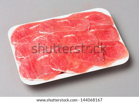 Sliced beef shank in foam tray isolated on gray background - stock photo