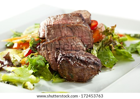 Sliced Beef Steak on Fresh Salad Leaf with Pesto Sauce - stock photo
