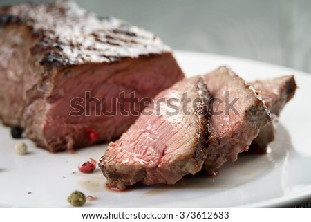 sliced beef steak on white plate close up - stock photo