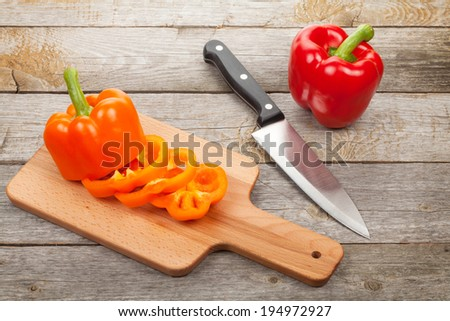 Sliced bell pepper on cutting board over wooden table - stock photo
