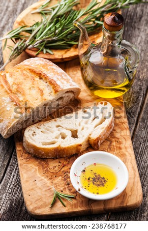 Sliced bread Ciabatta and extra virgin Olive oil on olive wood cookware background - stock photo
