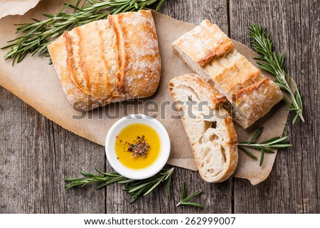 Sliced bread Ciabatta and extra virgin Olive oil on wooden background - stock photo