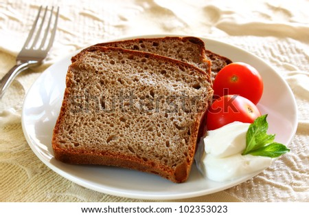 sliced bread  with spread cheese, decorated with a cherry tomato - stock photo