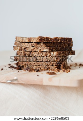 Sliced Brown Unleavened Bread from a Rough Grinding with Muesli, Nuts and Sesame Seeds on a chopping board - stock photo