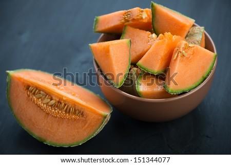 Sliced cantaloupe melon, dark wooden background - stock photo