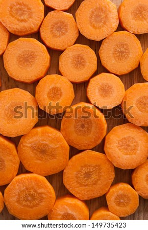 Sliced carrot against wooden chopping board background - stock photo