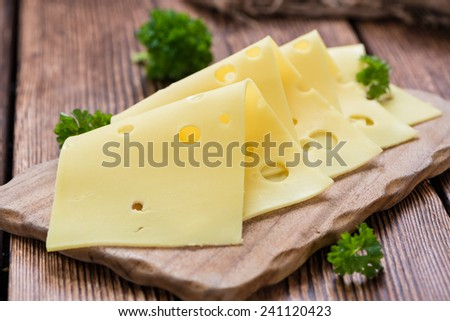 Sliced Cheese (close-up shot) on vintage wooden background - stock photo