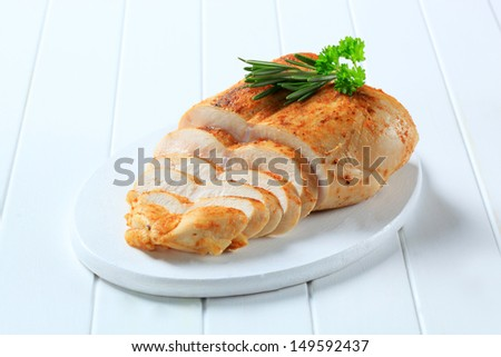sliced chicken breast with fresh herbs on a cutting board - stock photo