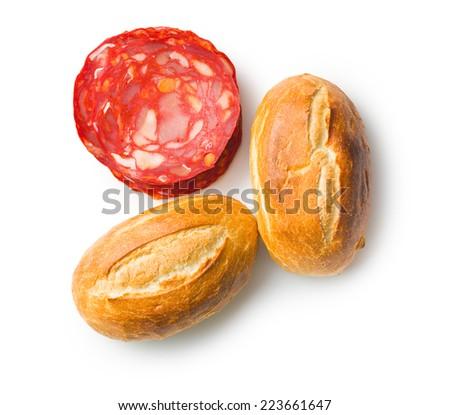 sliced chorizo salami and buns on white background - stock photo