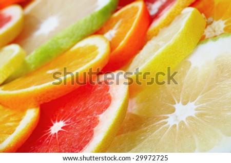Sliced citrus fruits background closeup - stock photo