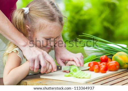 sliced cucumber. Mother teaches daughter  knife cut cucumber - stock photo