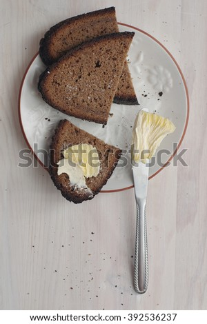 Sliced dark rye bread with knife and piece of butter on white dish. Light wooden background. View from top. Popular daily product for baltic countries. Export commodity of Latvia. - stock photo
