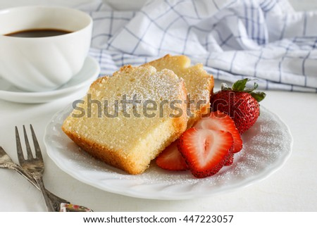Sliced delicious pound cake with fresh strawberries and icing sugar for breakfast served with hot espresso in white cup. - stock photo