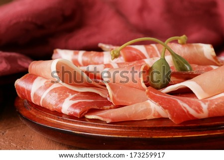 sliced dried sausage meat (ham, prosciutto, salami) served on a wooden board - stock photo