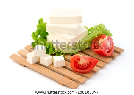 Sliced feta cheese with salad and tomatoes - stock photo