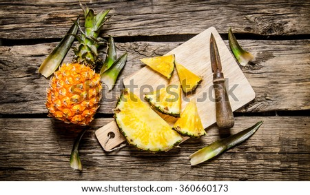 Sliced fresh pineapple with a knife on a chopping Board. On wooden background.  Top view - stock photo