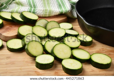 Sliced fresh zucchini with a cast iron skillet - stock photo