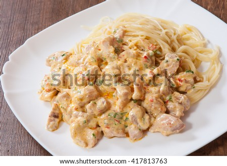 Sliced fried chicken meat in a creamy sauce with spaghetti pasta in a plate on wooden table - stock photo