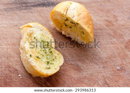 Sliced garlic bread on a wooden surface - stock photo