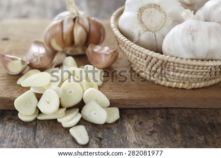 sliced garlic, garlic clove, garlic  bulb in wicker basket place on chopping block on vintage wooden background - stock photo