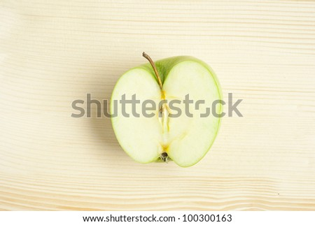 sliced green apple on wooden table - stock photo