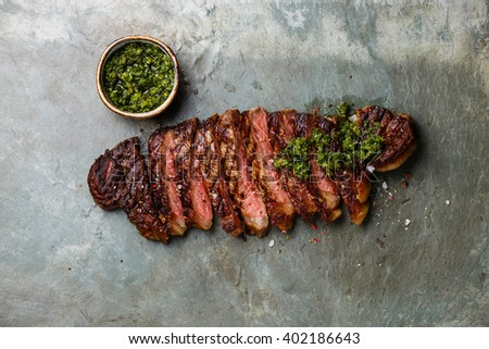 Sliced grilled beef barbecue Striploin steak with chimichurri sauce on gray stone slate background - stock photo