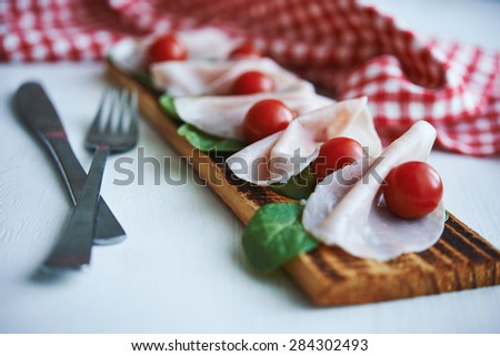 sliced ham with tomatoes on wooden board - stock photo
