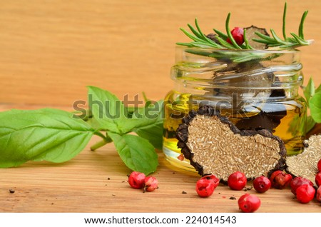 Sliced heart shaped black truffle in olive oil in small jar and some fresh spices, basil, oregano, rosemary and red pepper, close up view - stock photo