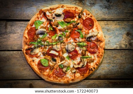 Sliced home made pepperoni pizza on wooden rustic background - stock photo