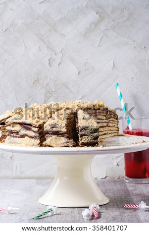 Sliced Homemade Birthday Honey Cake with chocolate cream, served on white ceramic plate over white wooden table with b-day candles and glass of red juice. With plastered wall as background. - stock photo