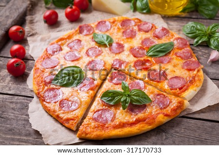 Sliced homemade Italian traditional pepperoni pizza with basil, salami, mozzarella cheese and tomato sauce on vintage wooden table background. Rustic style and natural light. - stock photo