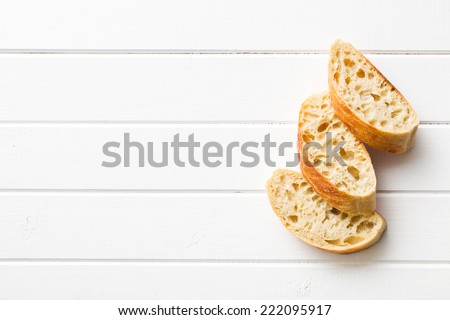 sliced Italian ciabatta on white wooden table - stock photo