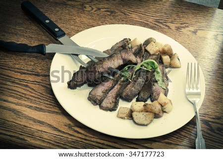 Sliced juicy skirt steak with potatoes and arugula garnish - stock ...
