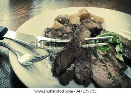 Sliced juicy skirt steak with potatoes and arugula garnish - stock ...