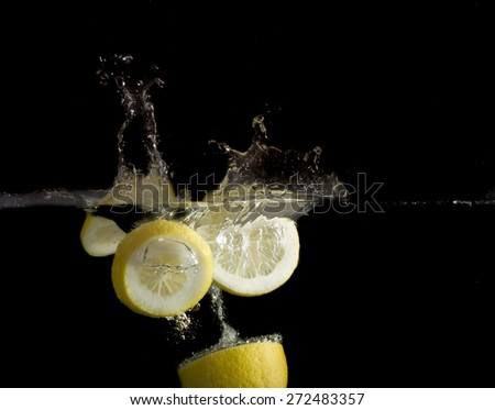 Sliced lemon in the water on black background - stock photo