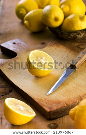 sliced lemons  on a cutting board on a wooden background - stock photo