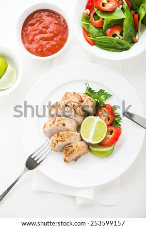 Sliced lime pork tenderloin with spinach salad on white background top view. - stock photo