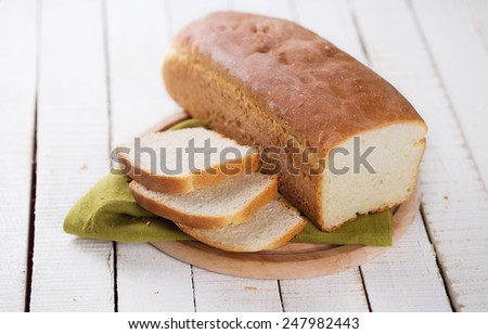 Sliced loaf of homemade  bread on board on white wooden background. Selective focus. - stock photo