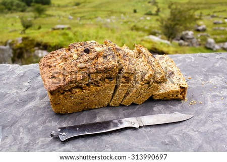 Sliced loaf of the fresh traditional Irish soda bread outside with knife aside and visible greenery on the background.  - stock photo