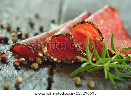 Sliced meat sausage salami on the wooden table with herbs and spices - stock photo