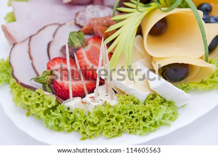 Sliced meat with cheese on a plate, isolated on a white background. - stock photo