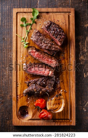 Sliced medium rare grilled Beef steak Ribeye with grilled onions and cherry tomatoes on cutting board on wooden background - stock photo