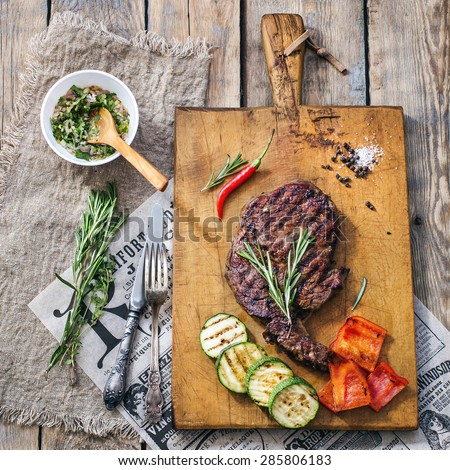 Sliced medium rare grilled Beef steak Ribeye with grilled vegetables and chilli peper on cutting board on wooden background with newspaper - stock photo
