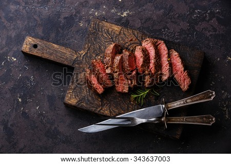 Sliced medium rare grilled Beef steak with knife and fork for meat on wooden cutting board background - stock photo