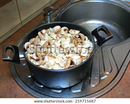 Sliced mushrooms and onions in the kettle         - stock photo