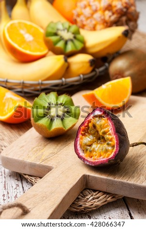 sliced passion fruit and tropical fruits in assortment: bananas, kiwi, pineapple, orange - stock photo