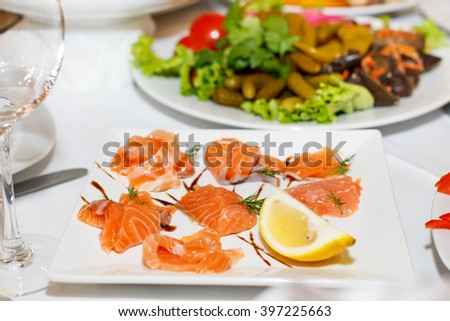 Sliced pieces of salmon and lemon on a white plate in a restaurant - stock photo