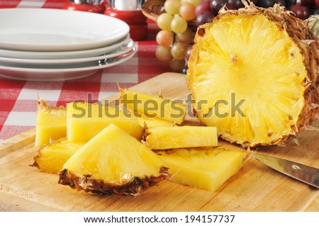 Sliced pineapple on a cutting board with a basket of fruit on a picnic table  - stock photo