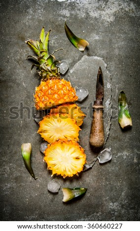 Sliced pineapple with a knife and leaves on a stone stand. On the stone table. Top view - stock photo